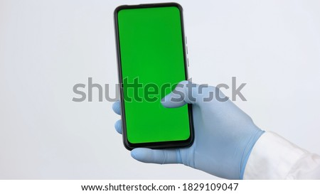 Photo of  Phone with green screen for chromakey. Close-up hand with smartphone on white background.