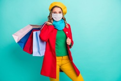 Phoro of positive cheerful girl hold bags wear mask green blue scarf headwear isolated over turquoise color background
