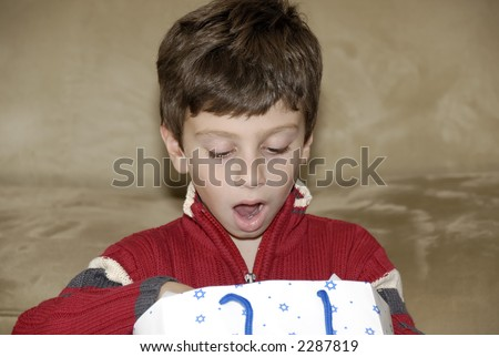 Phot of a Young Boy Looking at His Gift - Surprised Expression - stock photo