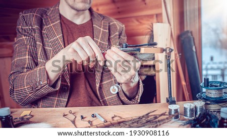 Phota Close up on young man's hands tying a fly for fishing Stock fotó ©