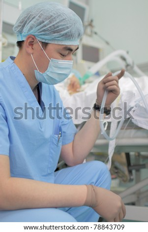 Photo a young Asian doctor in uniform; mask and cap near the bedside. Reflects the daily work in hospital;