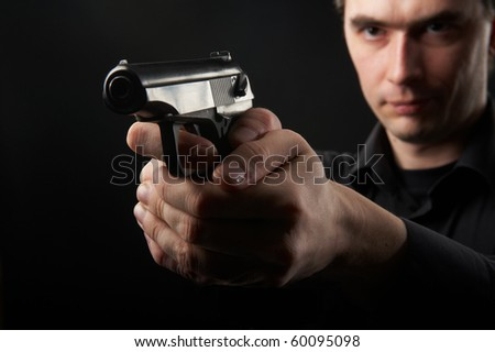 photo a young man drawing a gun in self defense studio shoot