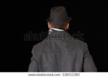 Photo about a man who wears a grey fabric jacket, hat and scarf. Viewed from behind.