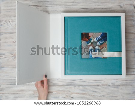Photo album in a cardboard box photobook with leather cover. photo book  on a white background. open box with photo album. photobook in a gift cardboard box