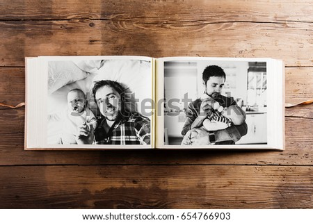 Photo album with pictures of father and baby son. Fathers day. #654766903