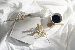 Photo album with white cloth reflecting natural light and shadows of leaves