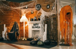 Photo area for Halloween with festive attributes. Fireplace, pumpkins, candles, skulls, bones, candles, chair, monsters decorations for Halloween indoors.