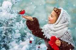 Photo as a postcard in vintage style depicting a small girl in a white downy shawl and red mittens, smiling and feeding a bullfinch bird from her hand, while white fluffy snow is falling around.