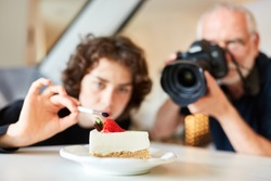 Photo assistant and photographer styling and photographing food