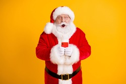 Photo astonished fairy fat grey beard santa claus use smartphone follow x-mas christmas discount news impressed wear stylish red costume belt isolated bright shine color background