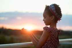 Photo at sunset. The child holds the sun in his palms. Against the background of the landscape. Portrait. Mixed race person, afro hair. The concept of happiness, stop racism, vacation, life, nature.