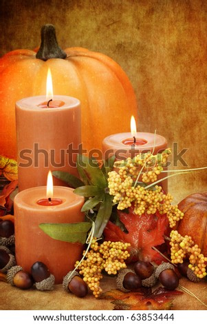 Photo based image of autumn still life of burning candles surrounded by colorful leaves, pumpkins and acorns.