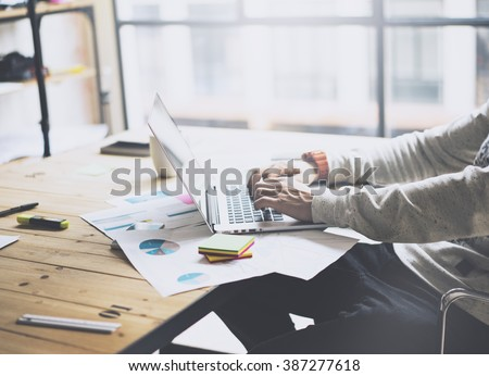Photo bearded businessman working with new project modern loft. Generic design notebook on wood table.  Analyze plans, papers, hands texting keyboard. Blurred background, film effect #387277618