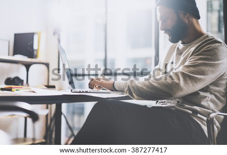 Photo bearded graphic designer working with new project modern loft. Generic design notebook on wood table.  Analyze plans, papers, hands keyboard. Blurred background, film effect