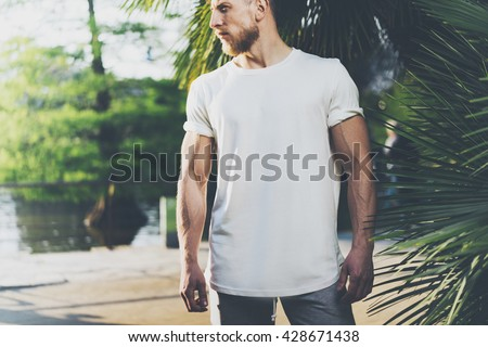 Shutterstock Photo Bearded Muscular Man Wearing White Blank t-shirt in summer time. Green City Garden, lake and palms Background,blurred. Horizontal Mockup
