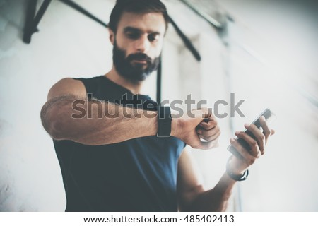 Photo Bearded Sportive Man After Workout Session Checks Fitness Results Smartphone.Adult Guy Wearing Sport Tracker Wristband Arm.Training hard inside gym.Horizontal bar background.Blurred #485402413