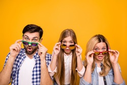 Photo beautiful mom lady handsome dad little school girl daughter taking off cool sun specs open mouth shocked staring expensive prices wear casual clothes isolated yellow color background