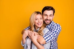 Photo beautiful wife lady handsome husband guy couple hugging good mood in love perfect pair hold arms wear casual shirts clothes isolated yellow color background