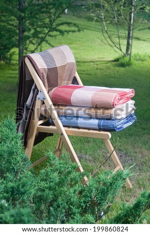 photo blankets folded on a chair outdoors