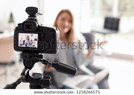 Photo blogger recording video indoors, selective focus on camera display. Space for text