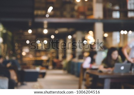 Photo blurred of coffee shop or modern library . Abstract, freelancer working on laptop in cafe with a cup of coffee.