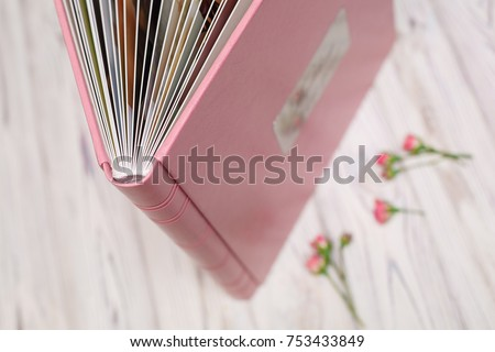 photo?book with a hard cover on a wooden surface pink photo album with leatherette with a shield Expanded photo book pages open photo album leather photo book in the box