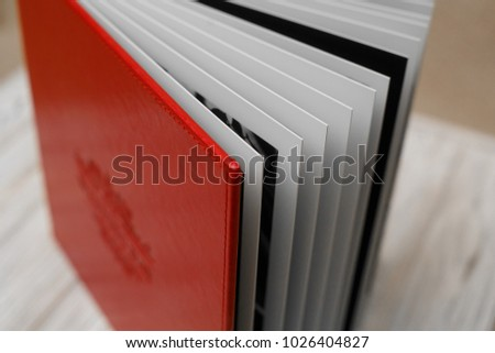 Photo book with embossing. Photobook on a light surface. Red photo book with  leather cover. Photo album with a hard cover. Bright red photoalbum. Photobook pages. background for photo publishingbackg