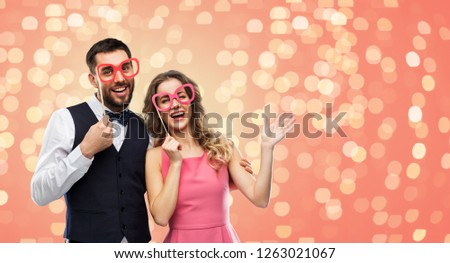 photo booth, fun and people concept - happy couple posing with party props over living coral background and festive lights