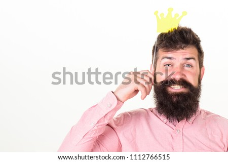 Photo booth fun concept. Man holding paper party props crown, white background. Hipster with beard and mustache on cheerful face posing with photo booth props, copy space. King in paper crown.