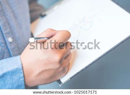Photo business man wearing suit, looking smartphone and holding documents in hands. Open space loft office,young business man reading sitting at the desk on office background #1025017171