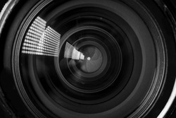 Photo Camera or Video lens close-up on black background, objective, concept of photographer camera man job, looking for a photographer, journalist, a videographer to work black and white