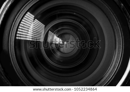 Photo Camera or Video lens close-up on black background, objective, concept of photographer camera man job, looking for a photographer, journalist, a videographer to work black and white #1052234864