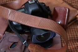 Photo camera with brown leather shoulder belt in brown background with leather accessories