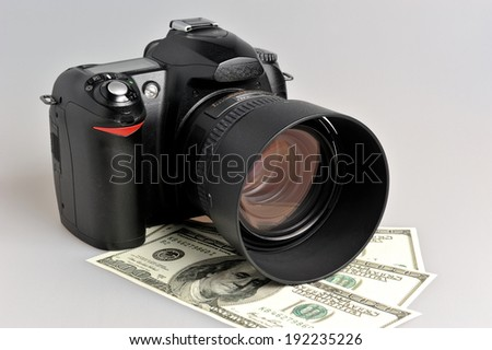 Photo camera with dollars on gray background