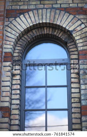 photo close-up of a window arch of the house with red brick.