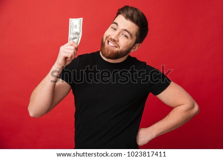 Photo close up of satisfied bearded man in black t-shirt demonstrating money bill 100 dollar currency on camera isolated over red wall