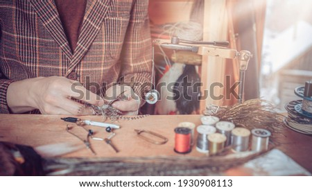 Photo Close up on young man's hands tying a fly for fishing Stock fotó ©