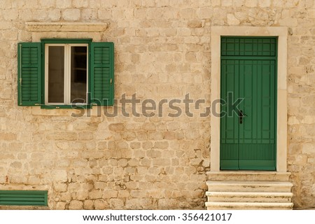 Photo closeup of old aged building made of beige stone masonry with green wooden door and shutters open window outside on cityscape background, horizontal picture