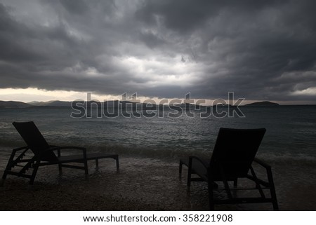 Photo closeup of two chaise lounges day beds standing on pebbles on beach at dusk low dark clouds bad weather grey sea shore against seascape background, horizontal picture