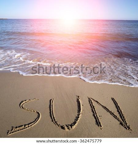 photo closeup with sun spot of word sun written on wet beige beach sea marine grained