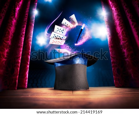 photo composite of a magic hat on a stage with cards and a magic wand