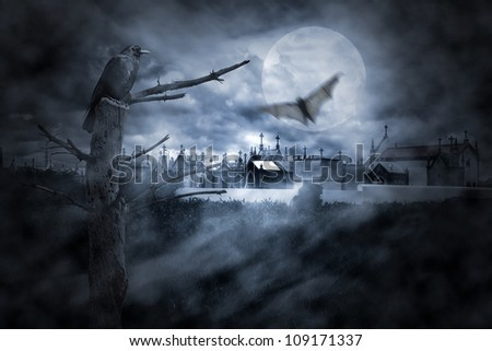 Photo composition with full moon at night, part of a naked tree, cemetery, clouds, fog, bat in flight and crow that can be used for halloween