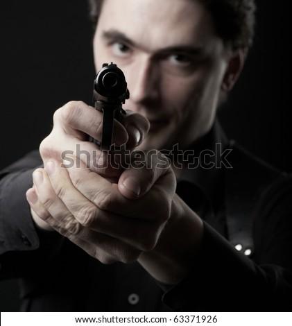 photo dark man pointing a gun looking at the camera
