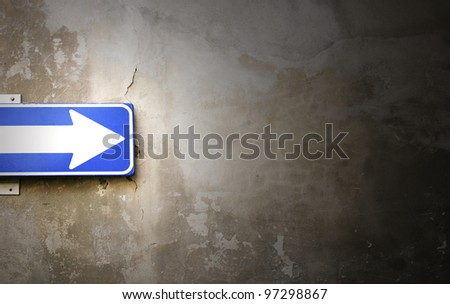 Photo detail of an arrow sign stuck on old wall crumbling