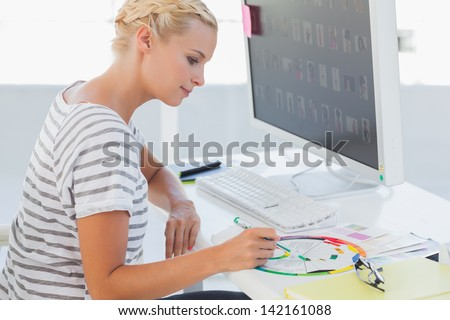 Photo editor pointing at a colour wheel in her office