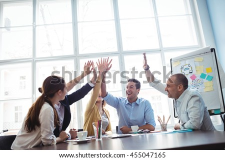 Photo editors giving high-five in meeting room at creative office