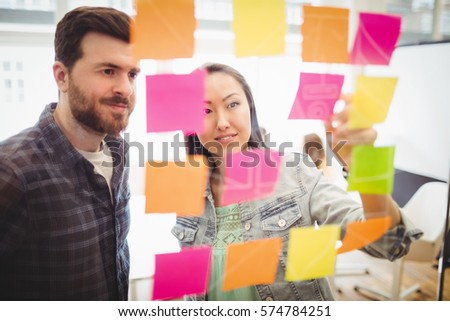 Photo editors looking at multi colored sticky notes on glass in meeting room at creative office