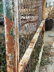 photo fence that is rusty. looks like an old and worn iron fence.
