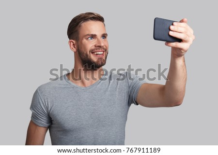 Photo for his girlfriend. Handsome young smiling man taking selfie while standing against grey background