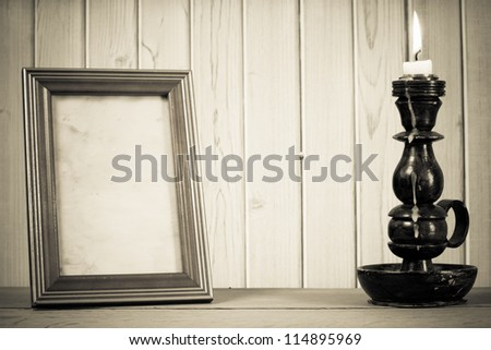 Photo frame and candlestick with burning candle in front of wooden background